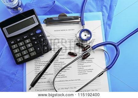 Medical stethoscope, clipboard, coat and calculator, close-up
