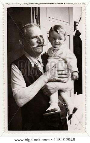 Vintage photo of a small girl with her grandfather circa 1941