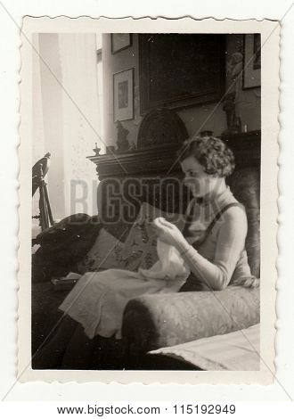 Vintage photo shows woman makes embroidery circa 1941.