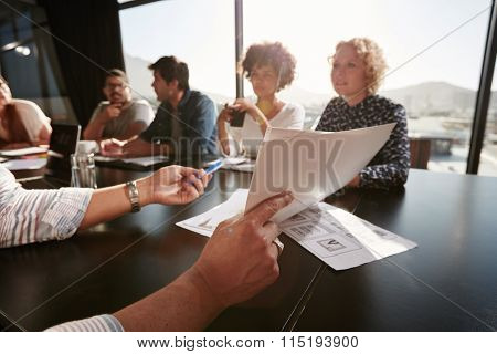 Papers In Hands Of Man Explaining Plan To Creative Team