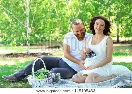 Handsome man and his lovely pregnant wife with blue baby booties  in the park