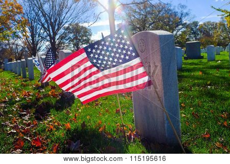 Arlington National Cemetery - Headstone and US National flag with lens flare - Washington DC, USA
