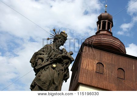 A View On Sandstone Religious Statue And Wooden Church Tower