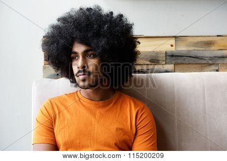 Young Black Guy With Afro Sitting At Home Thinking