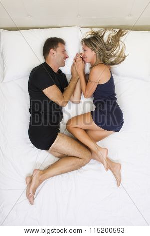 Peaceful And Smiling Couple Holding Hands In Bed