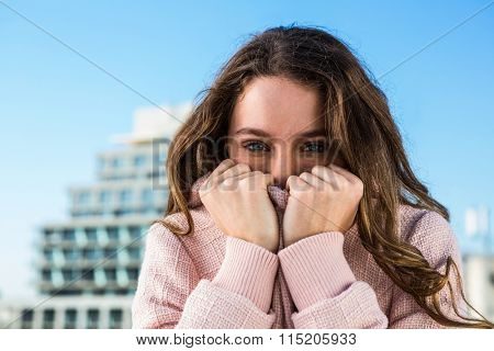 Young girl hiding her mouth with her sweater in town