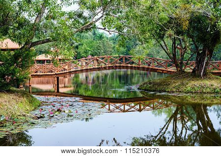 Beautiful Garden With Bridge And Reflection In The Lake