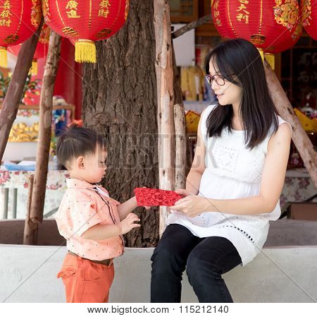 Asian Mother Give A Red Envelope Or Ang-pow  To Son