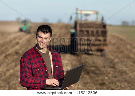 Farmer With Laptop And Tractors On Field