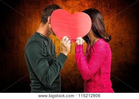 Couple covering faces with heart shape against shades of brown