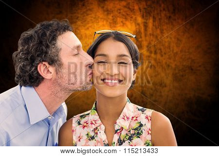 Man kissing woman on the cheek against shades of brown