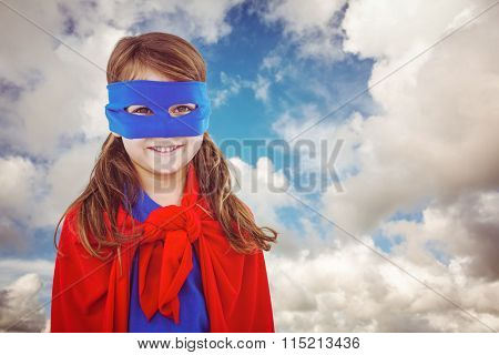 Masked girl pretending to be superhero against blue sky with white clouds
