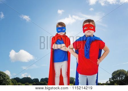 Masked kids pretending to be superheroes against green field