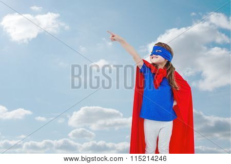 Masked girl pretending to be superhero against sky and clouds