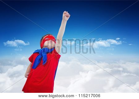 Masked boy pretending to be superhero on white screen against bright blue sky over clouds
