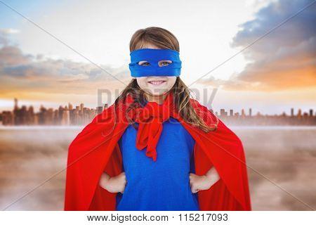 Masked girl pretending to be superhero against city on the horizon