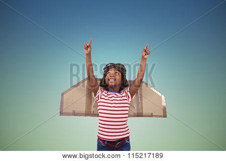 Smiling boy pretending to be pilot against blue sky