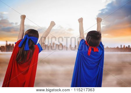 Masked kids pretending to be superheroes against city on the horizon