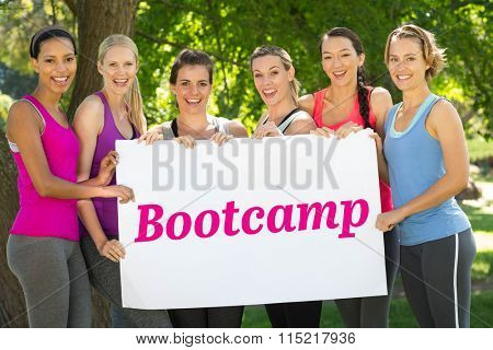 The word bootcamp and modern white and pink room with window against fitness group holding poster in park