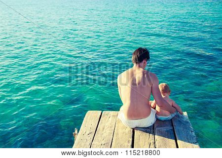 Young Father with His Son Relaxing by the Sea