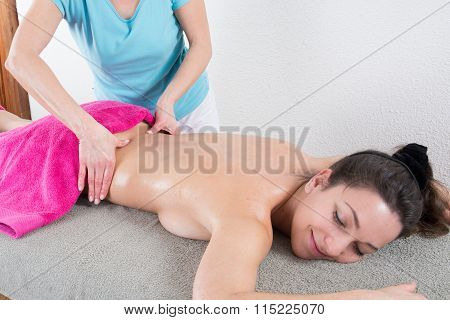 Qualified Therapist Doing Pressure Massage On A Woman's Hip