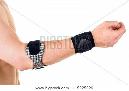 Man Wearing Wrist And Elbow Braces In Studio