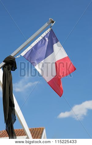 French Flag Against Blue Cloudy Sky.