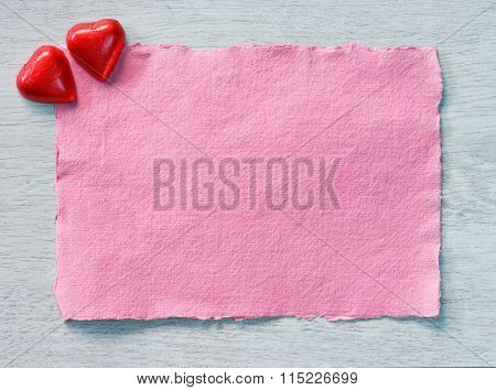 Valentine's Day candies and pink paper for text