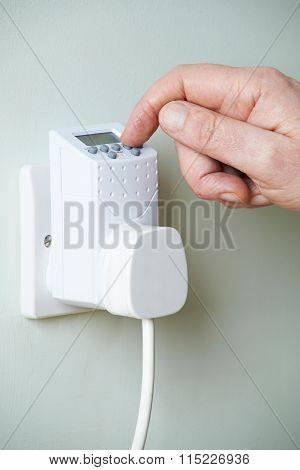 Close Up Of Hand Adjusting Timer Switch In Plug Socket