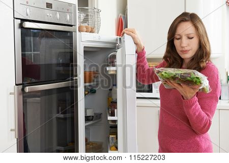 Woman Checking Sell By Date On Salad Bag In Refrigerator