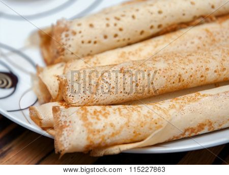 Delicious crepe rolls on white plate.