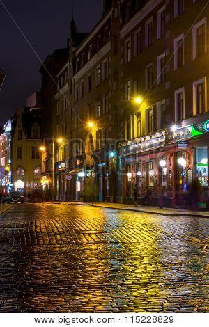 RIGA, LATVIA - DECEMBER 19, 2015: People walking in old town at evening on December 15, 2015 in Riga, Latvia