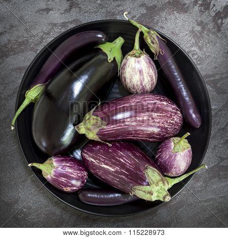 Eggplant varieties in black bowl over dark slate background.  Overhead view.