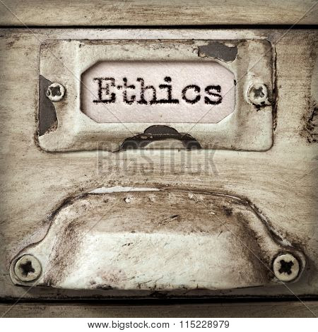 Word ethics on drawer label of vintage industrial filing cabinet.