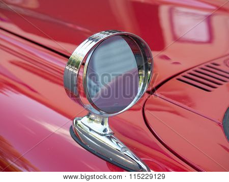 One Side Mirror On A Red Car
