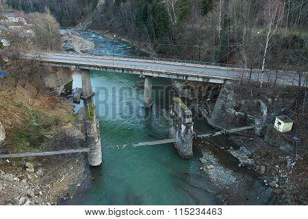 Highway And Damaged Pedestrian Suspension Bridge Across Mountain River