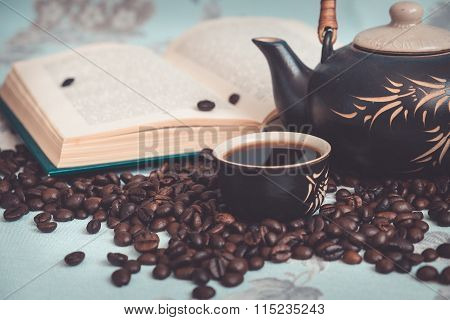 Cup of coffee, coffee beans, a teapot in the background of a open book