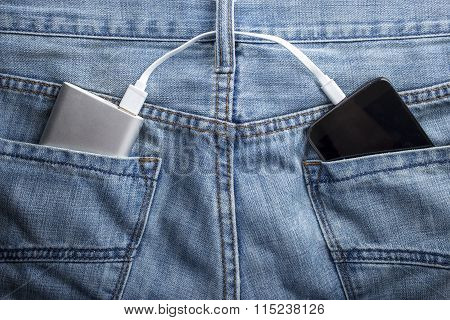 Power Bank Lies In A Back Pocket Of Jeans The Mobile Phone Charges