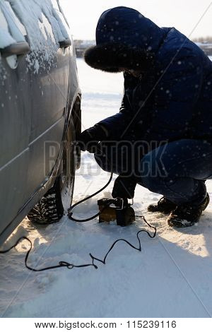 The Young Man Inflates The Wheel Of Car