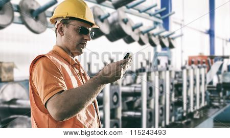 Worker With Protective Uniform In Front Of Production Machine