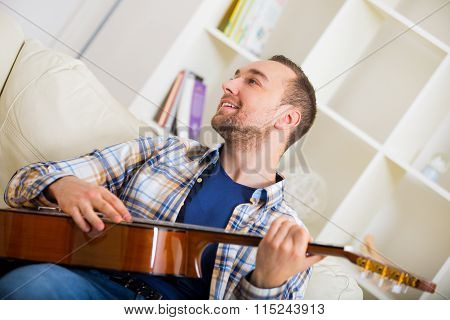 Portrait of a young man playing the guitar at home