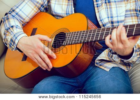 Young man playing the guitar at home, close up