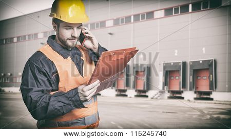 Worker With Protective Uniform In Front Of Shipping Warehouse Gates
