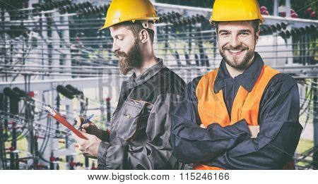 Smiling Workers With Protective Uniforms In Front Of Power Plant
