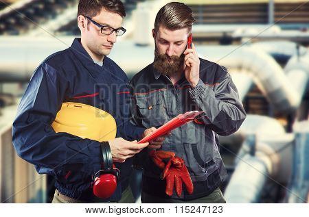 Workers In Protective Uniform With Smart Phone And Clipboard