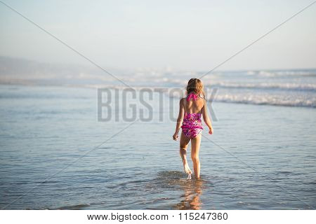 A young girl walks through shallow water