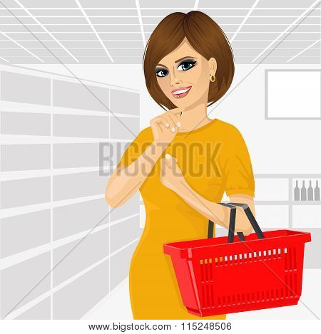 Thoughtful woman holding an empty shopping basket