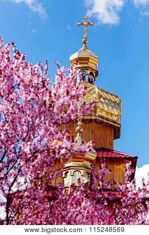 Kriviy Rih, Ukraine, April 22, 2015. Golden Domes Of Orthodox Churches And Purple Blossoming Magnoli