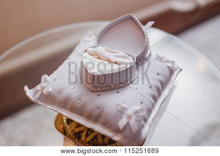 Wedding rings on the white heart pillow