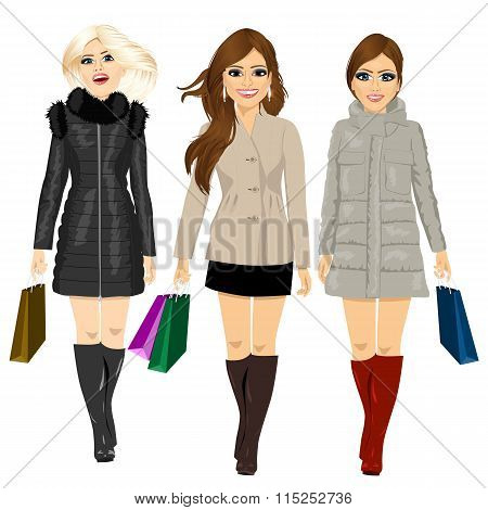 three young fashion women in autumn clothes walking forward holding shopping bags